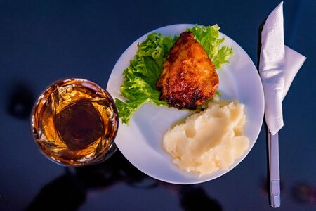 Close up plate with fried chicken thigh, salad and mashed potato and glass of apple juice. Selective focus Foto de archivo - 135487803