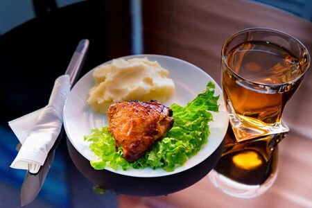 Close up plate with fried chicken thigh, salad and mashed potato and glass of apple juice. Selective focus Foto de archivo - 135487660