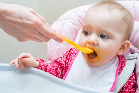 Feeding cute baby girl in pram with spoon