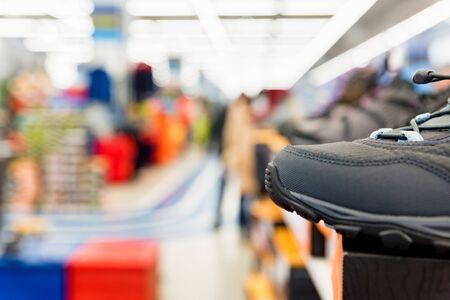 Close view of single sports shoe for sale in sports shop. Defocused background. Sports equipment concept Reklamní fotografie - 135494967