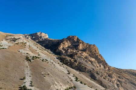 Rocks and dry grass in North Caucasus mountains in autumn on sunny day Фото со стока - 136168751