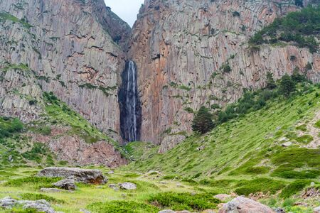 Summer landscape with mountain waterfall between two rocks Фото со стока - 136168757