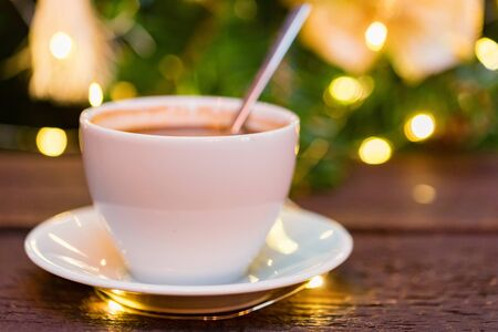 Cup of coffee with spoon with Christmas lights blur