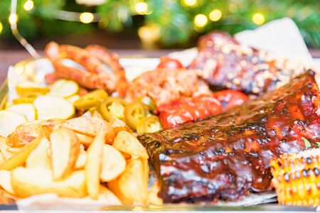 Dish of mixed meats. Grilled ribs, chicken and sausages served with baked potato