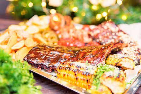 Plat de viandes mixtes. Côtes levées, poulet et saucisses grillés servis avec pomme de terre au four