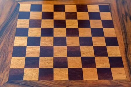 Close image of new wooden table with black and white cells for chess