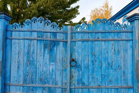 View of old Russian wooden gates in blue color with carvings on top