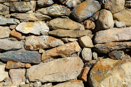 Close up of beige rough stone wall for abstract background Фото со стока