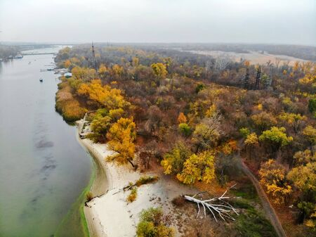 Sandy river bank and yellow trees in fall. Rustic countryside landscape in Russia taken by drone