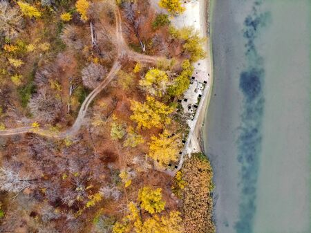 Drone picture of derelict abandoned concrete barge on river bank in fall Decaying alongside a river.