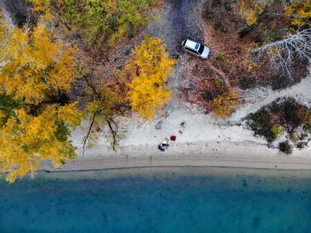 Top view two fishermen on left bank of Don river in late fall with beautiful blue water and bright trees. Taken by drone