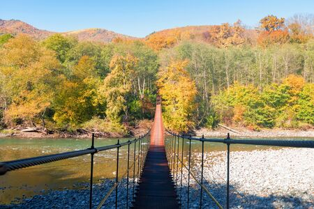 Beautiful landscape with narrow bridge made of metal going across the mountain river Фото со стока - 136271112