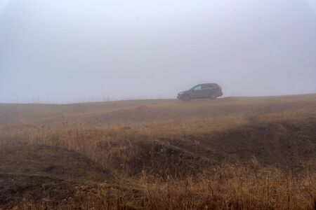 Depressing dark foggy countriside with car somewhere in Russia Фото со стока - 136281138