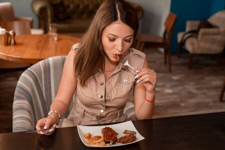 Beautiful girl enjoys chicken meal with beer in restaurant