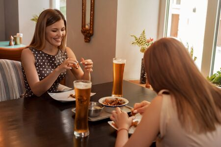 Two girl friends have coffee and dessert in modern restaurant