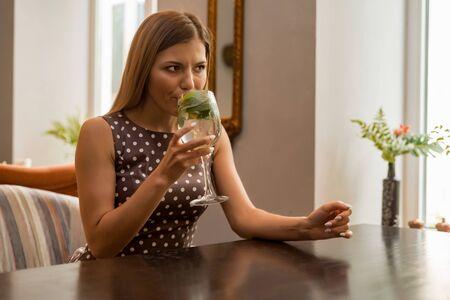 Beautiful girl enjoys mojito in cosy cafe Banco de Imagens