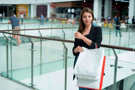 Beautiful smiling brown-haired girl with shopping bags and blurred mall Banco de Imagens