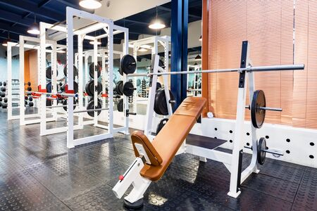 View of modern bench press exercise machine with barbell
