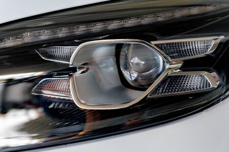 Close-up image of headlights of red sportcar