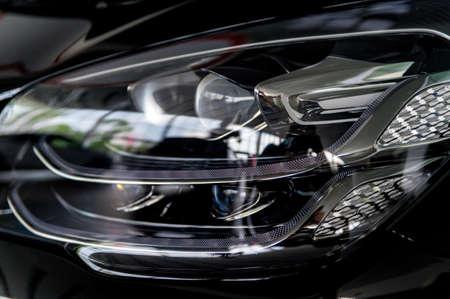 Close-up image of headlights of black premium car 免版税图像