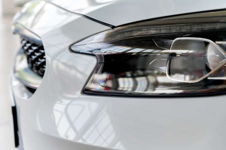Close-up image of headlights of white modern car