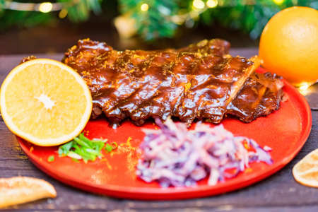 Close up roasted pork ribs in orange sauce served with lemon and vegetables Reklamní fotografie