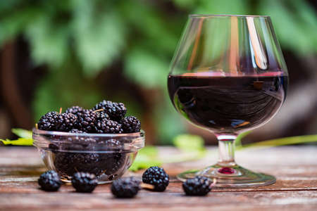 Close up fresh mulberries fruit in bowl and wine in glass Reklamní fotografie