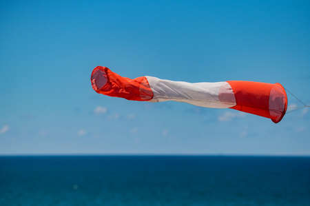Red and white windsock on a background of blue sky Reklamní fotografie