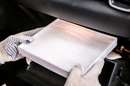 Hand of mechanik is holds new car cabin filter Stock Photo