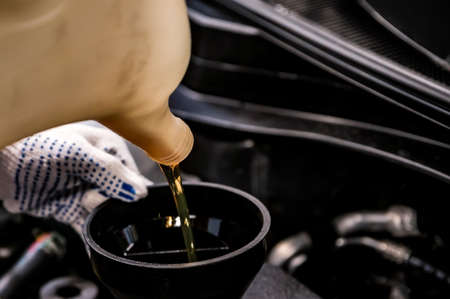 Close-up of oil change in a car during service.
