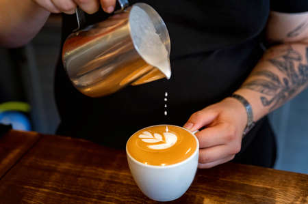 Man making cappuccino or latte with flower on froth.