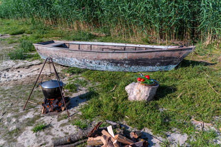 Fishing boat, bowler hat and fresh Ingredients for fish broth soup.