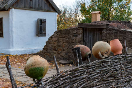 Clay jugs on a wooden fence of traditional houses and cossack family courtyard