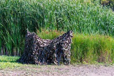 Camouflage tent for ambush in the reeds by the river