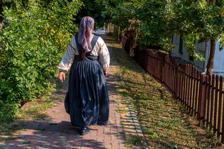 Woman in traditional Russian clothes walks along a wooden fence Foto de archivo