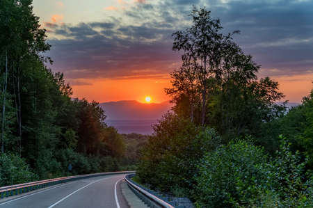 Picturesque landscape with sunset and narrow road in summer mountains 스톡 콘텐츠