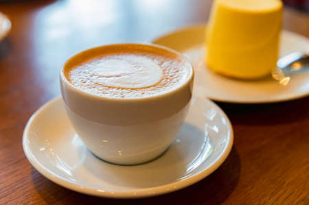 Cup of coffee with yellow cake on the background. Cappuccino