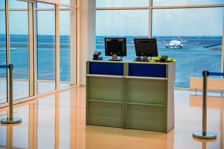 Empty little check-in desks with computers in airport