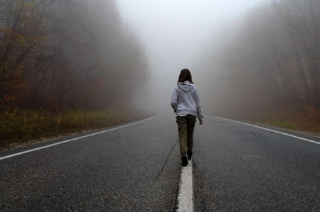 Young woman traveler, rear view on foggy road in autumn forest