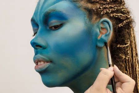Makeup Artist applies ye shadows to a beautiful woman in Avatar style
