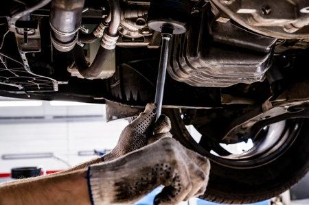 Car mechanic checks oil filter on Service station.