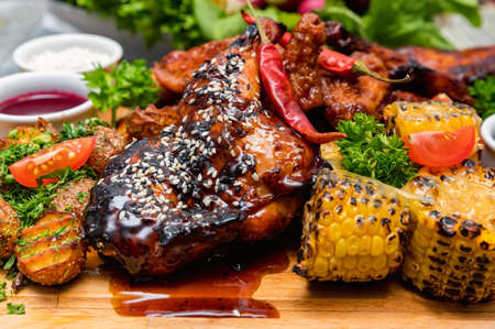 Barbecue chicken with vegetables on wooden table