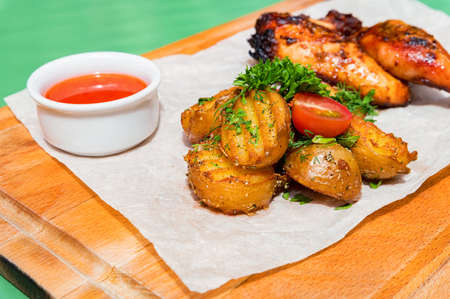 Juicy BBQ chicken leg quarters with fried potato. Food to go