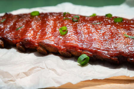 Close up board with pork ribs grilled with BBQ sauce, peanuts and jalapeno
