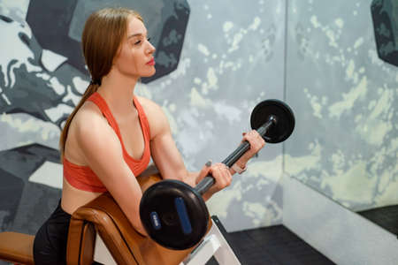 Sporty young beautiful blonde woman holds barbell in gym