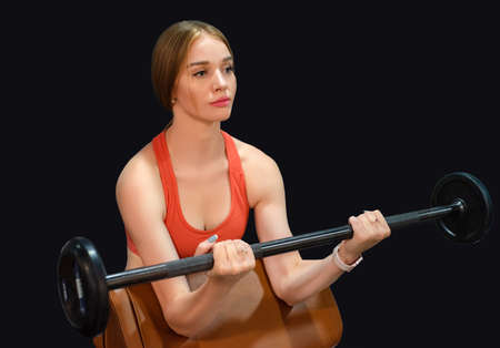 Sporty young beautiful blonde woman holds barbell in gym on black background