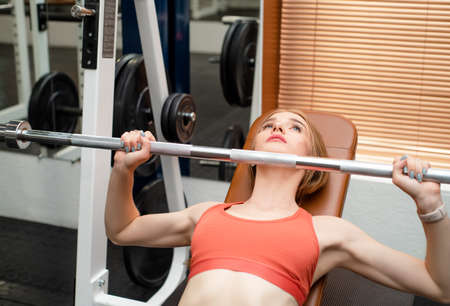 Young woman does bench press workout in modern gym Фото со стока