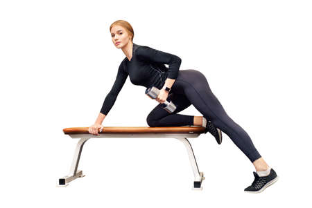 Beautiful young woman trains deltoid on bench in gym isolated on white