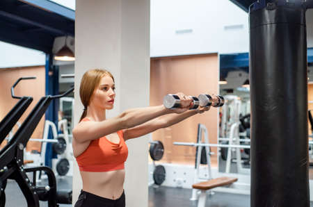 Beautiful young woman trains deltoid in gym with dumb-bell