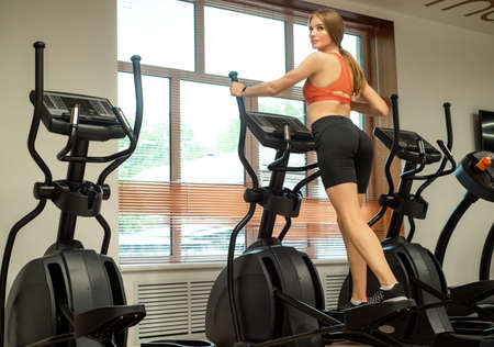 Close up female back view on elliptical trainer in gym